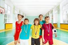 Szczęśliwi futbolowi zwycięzcy z medalami w sport sala Obraz Stock