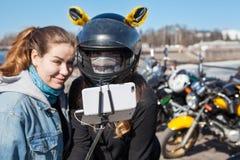 Szczęśliwi i uśmiechnięci żeńscy motocykliści biorą selfies używać smartphone z rozciągliwym monopod, ostrość na telefonie komórk fotografia stock