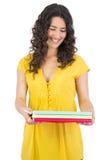 Szczęśliwi kędzierzawi z włosami brunetki mienia notatniki Fotografia Stock