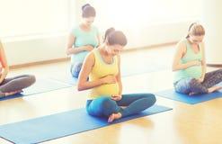 Szczęśliwi kobieta w ciąży ćwiczy joga w gym Zdjęcia Stock