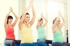 Szczęśliwi kobieta w ciąży ćwiczy na fitball w gym Zdjęcie Royalty Free