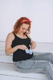 Szczęśliwi kobieta w ciąży mienia brzuszka łupy z czerwonym bandażem na jego głowie, Na lekkim tle Brzemienność miedzianowłosa Obrazy Royalty Free