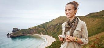 Szczęśliwi kobieta wycieczkowicza writing sms przed widok na ocean krajobrazem obraz royalty free