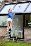 Szczęśliwi kobiety cleaning okno outdoors zdjęcia stock