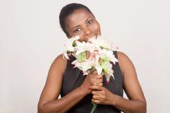 Szczęśliwi kobiety mienia kwiaty i karta Fotografia Stock