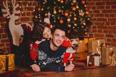 Szczęśliwi kochający młodzi ludzie i mops są prześladowanym mieć zabawę blisko choinki Uśmiechnięta para świętuje nowego roku sto Obraz Royalty Free