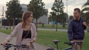 Szczęśliwi kochankowie chodzą wpólnie w parku, stacza się ich rowery blisko zbiory