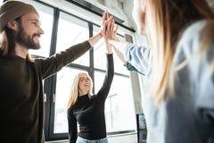 Szczęśliwi koledzy w biurze dają wysokości pięć each inny Zdjęcie Royalty Free