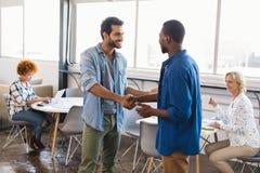 Szczęśliwi ludzie biznesu trząść ręki przy kreatywnie biurem Zdjęcia Royalty Free