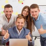 Szczęśliwi ludzie biznesu zespalają się wpólnie blisko laptopu w biurze obrazy royalty free