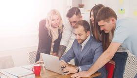 Szczęśliwi ludzie biznesu zespalają się wpólnie blisko laptopu w biurze Zdjęcie Stock