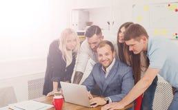 Szczęśliwi ludzie biznesu zespalają się wpólnie blisko laptopu w biurze Obraz Royalty Free