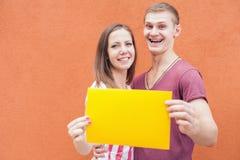 Szczęśliwi ludzie patrzeje i trzyma ramowy przy czerwonym tłem Obraz Royalty Free