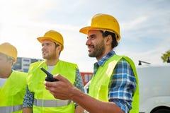 Szczęśliwi męscy budowniczowie w kamizelkach z walkie talkie Fotografia Royalty Free