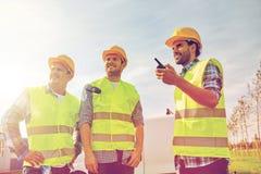 Szczęśliwi męscy budowniczowie w kamizelkach z walkie talkie Zdjęcie Royalty Free