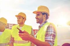 Szczęśliwi męscy budowniczowie w kamizelkach z walkie talkie Zdjęcie Stock