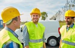 Szczęśliwi męscy budowniczowie w wysokich widocznych kamizelkach outdoors Zdjęcie Royalty Free