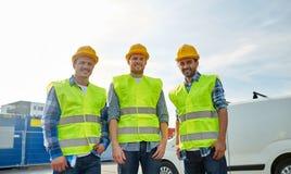 Szczęśliwi męscy budowniczowie w wysokich widocznych kamizelkach outdoors Zdjęcia Stock