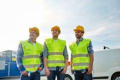 Szczęśliwi męscy budowniczowie w wysokich widocznych kamizelkach outdoors Fotografia Stock