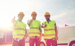 Szczęśliwi męscy budowniczowie w wysokich widocznych kamizelkach outdoors Zdjęcia Royalty Free