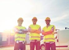 Szczęśliwi męscy budowniczowie w wysokich widocznych kamizelkach outdoors Obrazy Stock