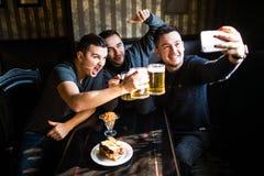 Szczęśliwi męscy przyjaciele bierze selfie i pije piwo przy barem lub pubem Fotografia Stock