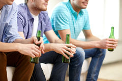 Szczęśliwi męscy przyjaciele z piwnym ogląda tv w domu obrazy royalty free