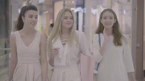 Szczęśliwi młoda dziewczyna przyjaciele chodzi w zakupy centrum handlowym zbiory