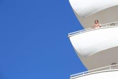 Szczęśliwi młoda kobieta stojaki na balkonie obraz stock