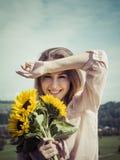 Szczęśliwi młodej kobiety mienia słoneczniki obrazy stock
