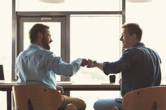 Szczęśliwi młodociani faceci współpracuje wpólnie przy pracą w biurze obraz stock