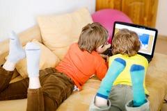 Szczęśliwi młodsi bracia, urocze dzieciak chłopiec ogląda telewizję podczas gdy kłamający Zdjęcia Royalty Free