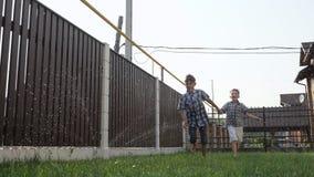 Szczęśliwi młodszy bracia cieszą się życie i biegający wzdłuż zieleń ogródu zdjęcie wideo