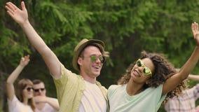 Szczęśliwi młodzi faceci podnosi ręki, machający kamera, tanczy przy przyjęciem, zwolnione tempo zbiory