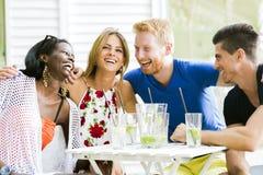 Szczęśliwi młodzi ludzie śmia się istotę szczęśliwą przy stołem Obrazy Royalty Free