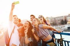 Szczęśliwi młodzi ludzie bierze selfies zdjęcia stock