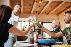 Szczęśliwi młodzi ludzie clinking szkła i świętuje przy stołem Obrazy Stock