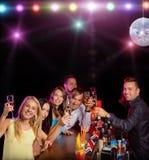 Szczęśliwi młodzi ludzie clinking z szampanem wewnątrz Fotografia Stock