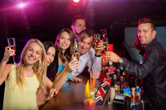 Szczęśliwi młodzi ludzie clinking z szampanem wewnątrz Zdjęcia Stock