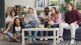 Szczęśliwi młodzi ludzie przyjaciół ogląda TV opowiadać popkorn wpólnie i jeść zbiory