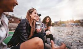 Szczęśliwi młodzi ludzie relaksuje jeziorem Fotografia Royalty Free