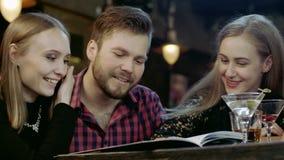 Szczęśliwi młodzi ludzie siedzi w prętowej czytelniczej menu karcie zbiory wideo