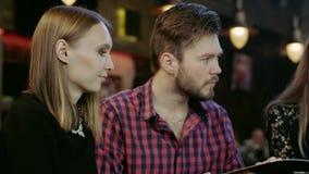 Szczęśliwi młodzi ludzie siedzi w prętowej czytelniczej menu karcie zdjęcie wideo