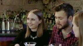 Szczęśliwi młodzi ludzie siedzi w prętowym czytelniczym menu karcianym i daje rozkazom męski kelner zbiory wideo