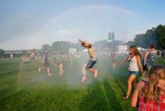 Szczęśliwi młodzi ludzie skacze w deszczu na plenerowym przyjęciu Zdjęcia Stock