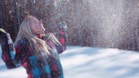 Szczęśliwi młodzi ludzie w kolorowej zimie są ubranym rzucać up śnieg w jaskrawym świetle słonecznym dzieciństwo creek kwiaty bab zbiory