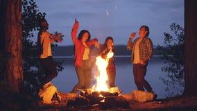 Szczęśliwi młodzi ludzie w przypadkowej odzieży tanczą wokoło ogienia w lesie ma zabawę i śmia się cieszący się muzykę, świeżą zbiory