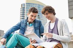 Szczęśliwi młodzi męscy studenci collegu używa cyfrową pastylkę przeciw budynkowi Zdjęcia Stock