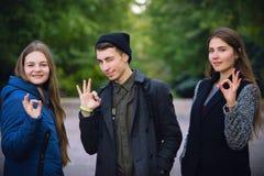 Szczęśliwi młodzi nastolatkowie przy jesień seansu parkowym ok podpisują zdjęcia stock