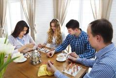 Szczęśliwi młodzi przyjaciele bawić się grę planszowa wpólnie Obrazy Stock
